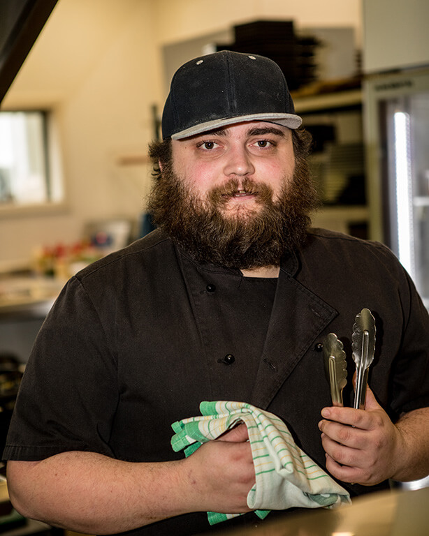The Fat Duck Te Anau's Junior Sous Chef, Josh Raynel, holding a tea towel and some tongs in the kitchen