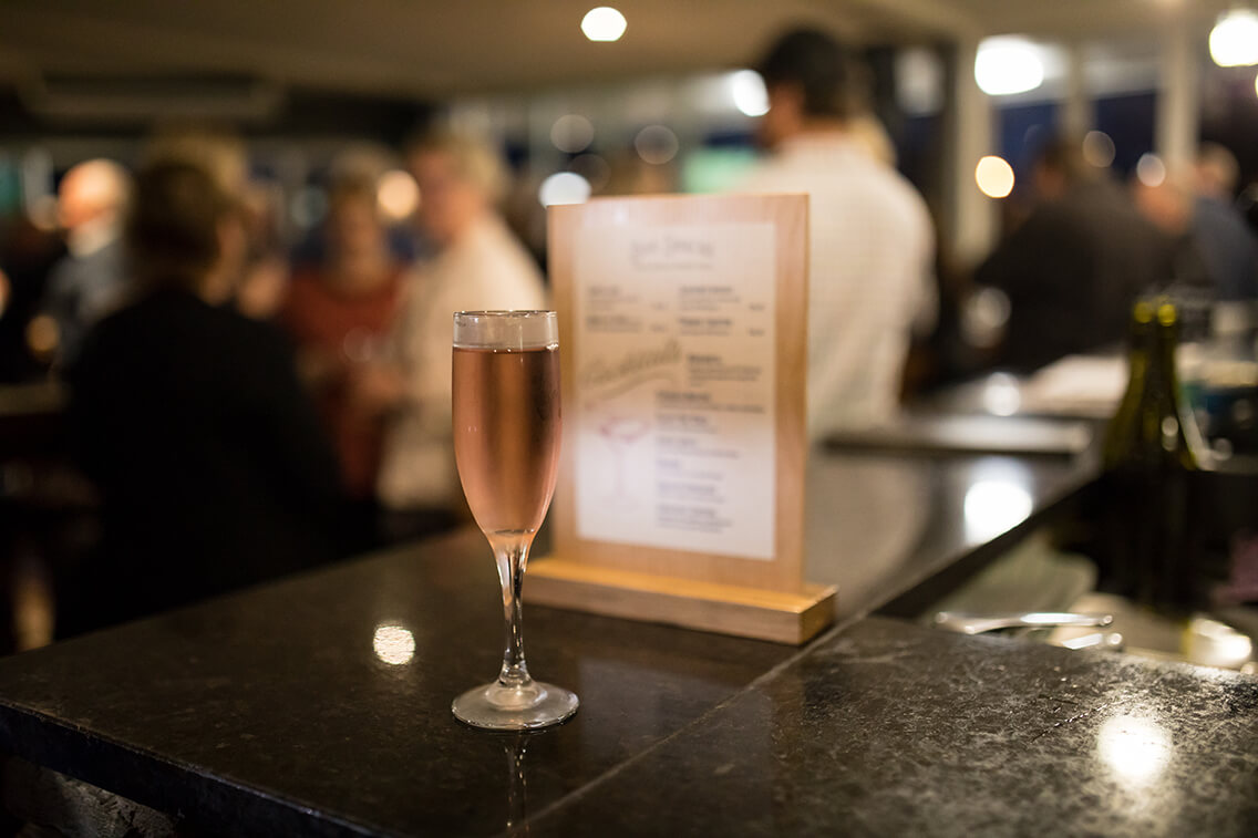 Glass of Rosé wine sitting atop the Fat Duck bar counter with a busy bar scene blurred into the background.
