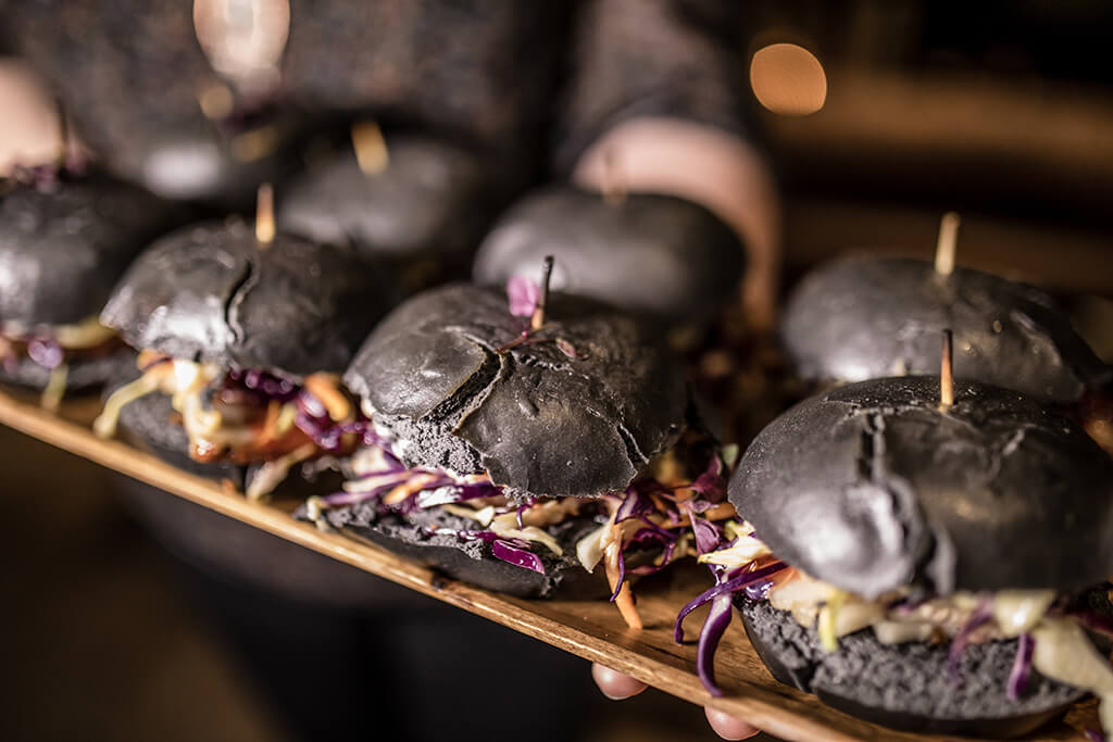 Charred black bao buns with Pork Belly and coleslaw inside atop a wooden platter