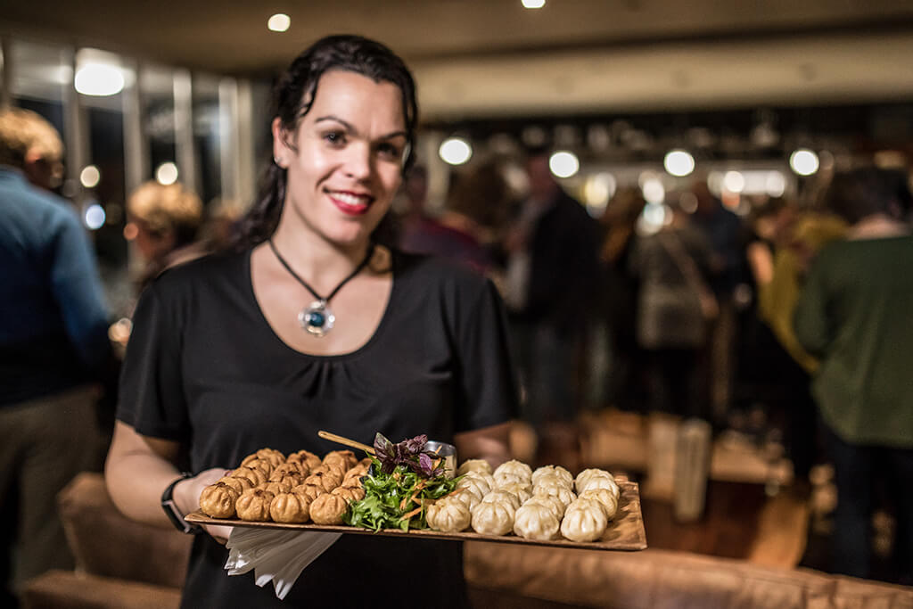 A waitress presenting a platter with Dumplings and a green garnish at a function being held at the Fat Duck Te Anau