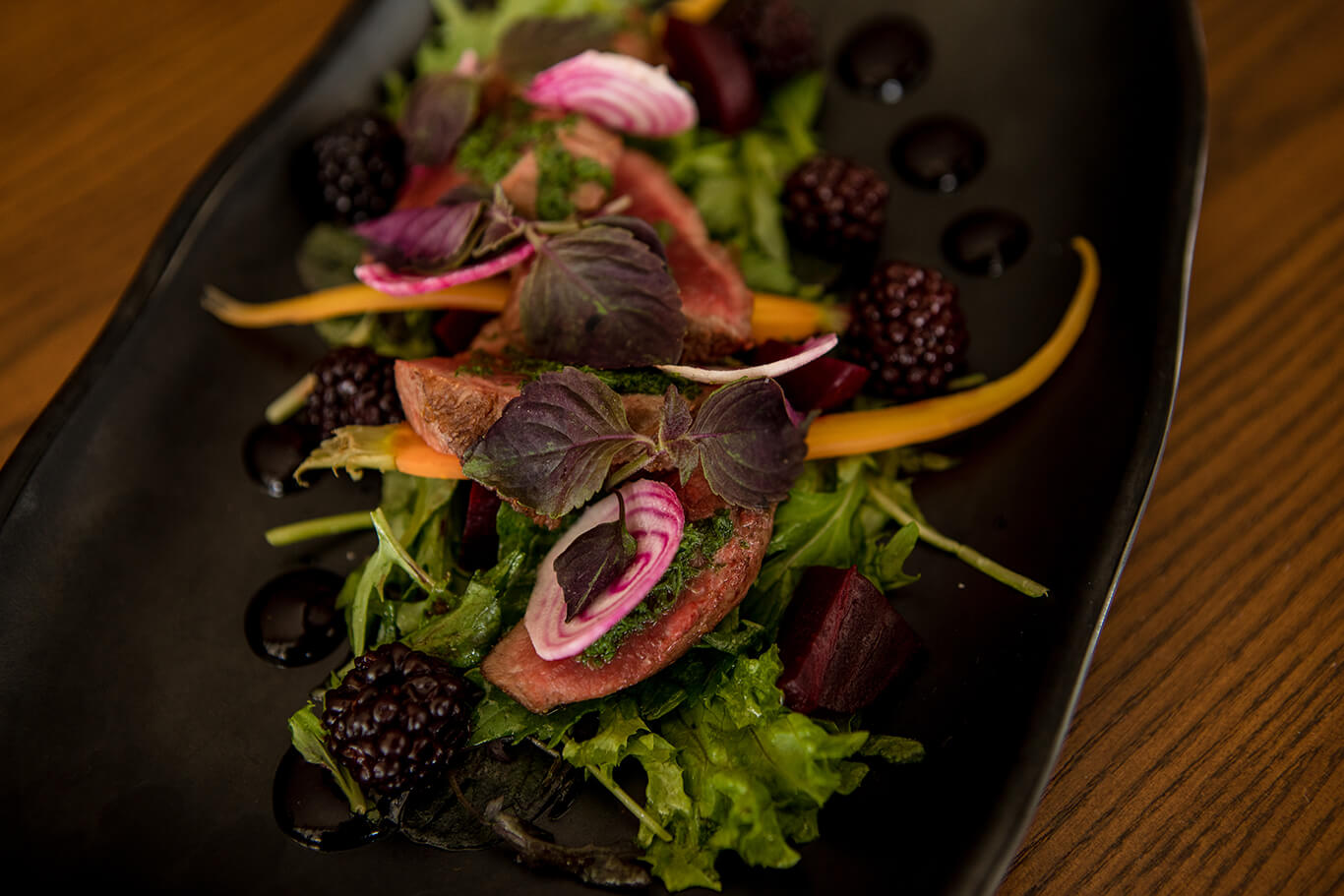 A plate of salad greens topped with Venison and surrounded by blackberries and beetroot.