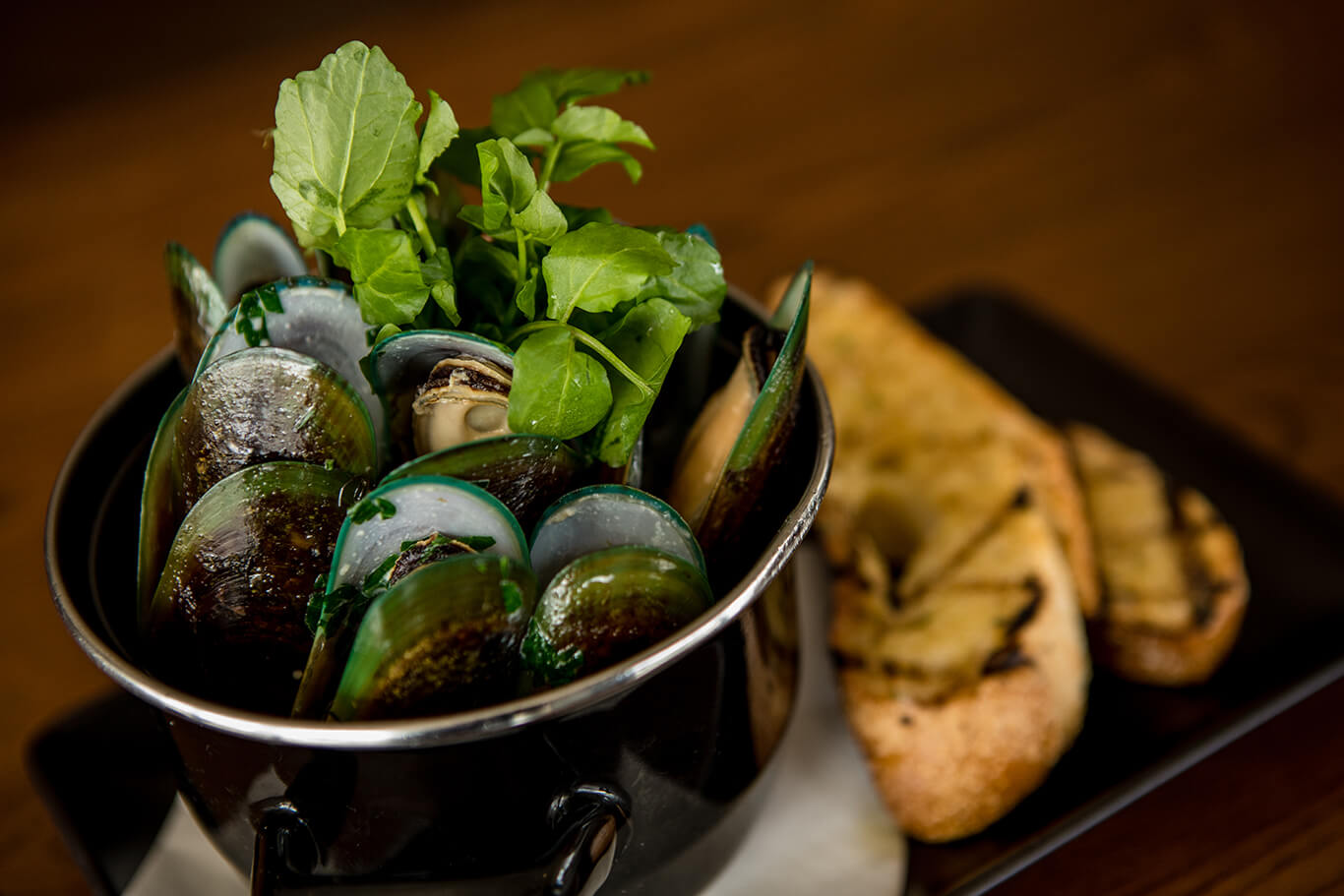 Green lipped mussels served in a small pot with a side of bread
