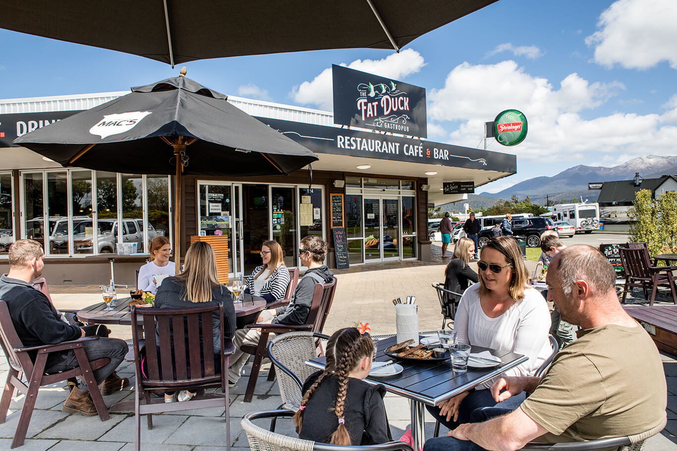 Three tables of diners enjoying the outdoor dining area at Te Anau's Fat Duck restaurant