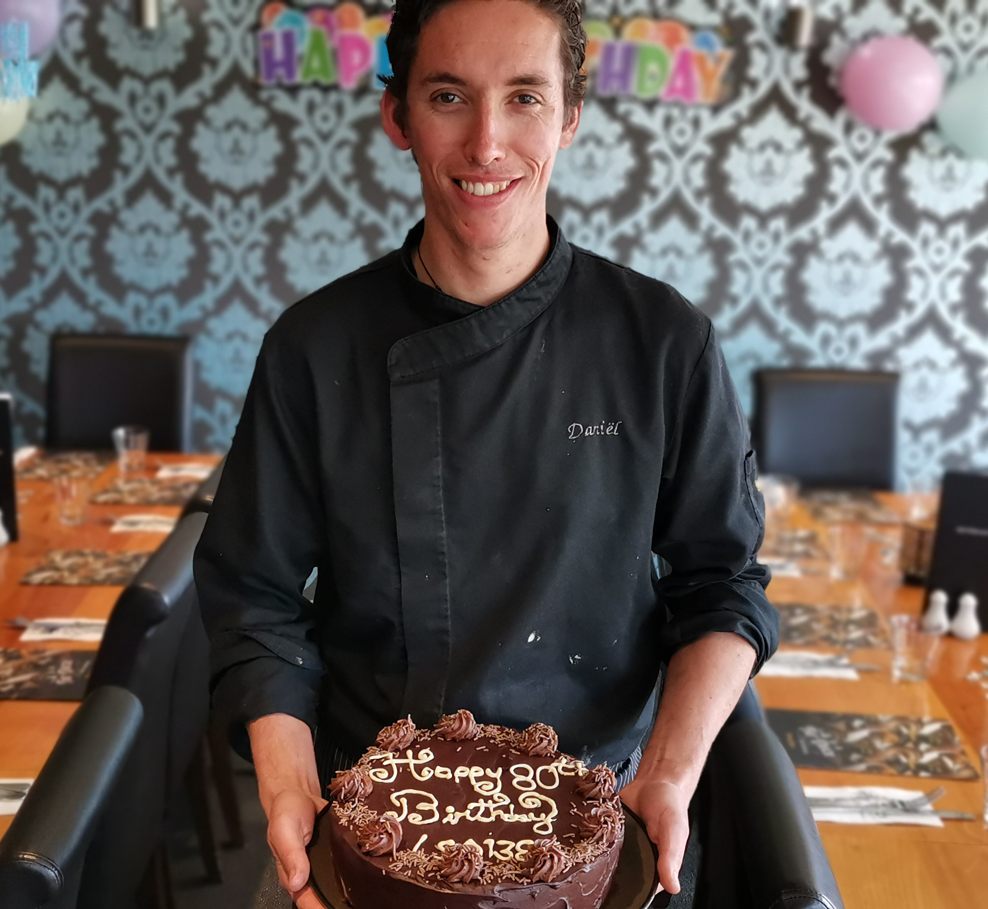 Chef Daniel proudly showing a chocolate cake with 'Happy 80th Birthday' inscribed in icing on the top