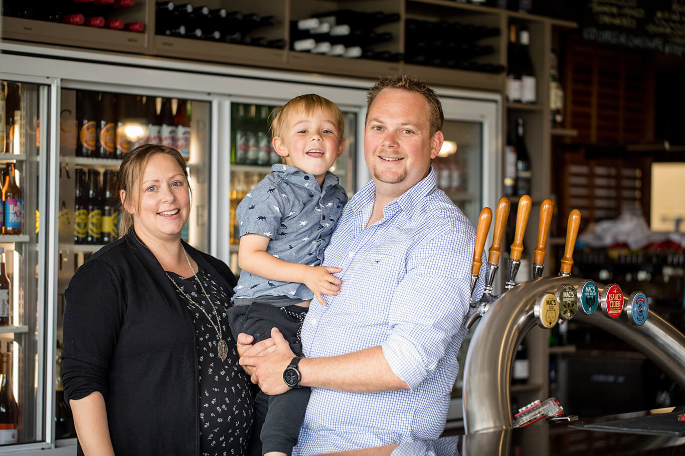 Owners of the Fat Duck Gastropub Te Anau, Cam, Selina and Eli, standing at the Fat Duck bar